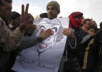 A protester in Tobruk holds a cartoon of Gaddafi