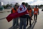 A Tunisian volunteer welcomes returning compatriots at the Rad Jdir border post